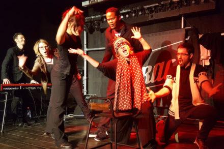 groupe improvisant une comédie musicale sur scène
