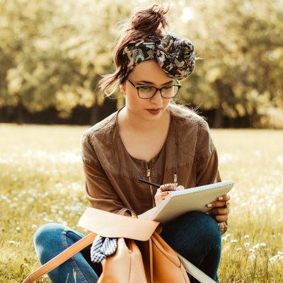 jeune fille écrivant dans un parc