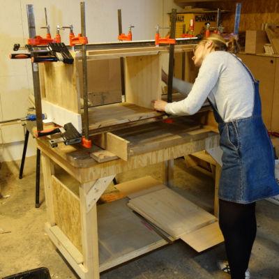 personne réalisant un meuble en bois et serrant les panneaux avec des serre joint