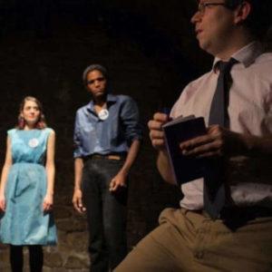 acteurs sur scène écoutant le metteur en scène
