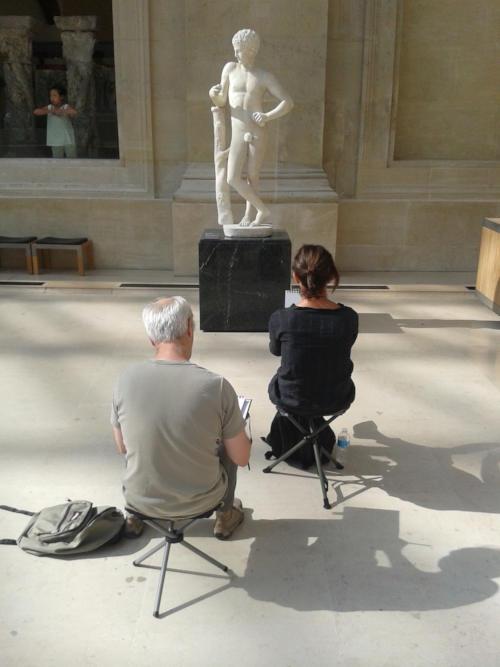 dessinateurs au louvre face à une statue