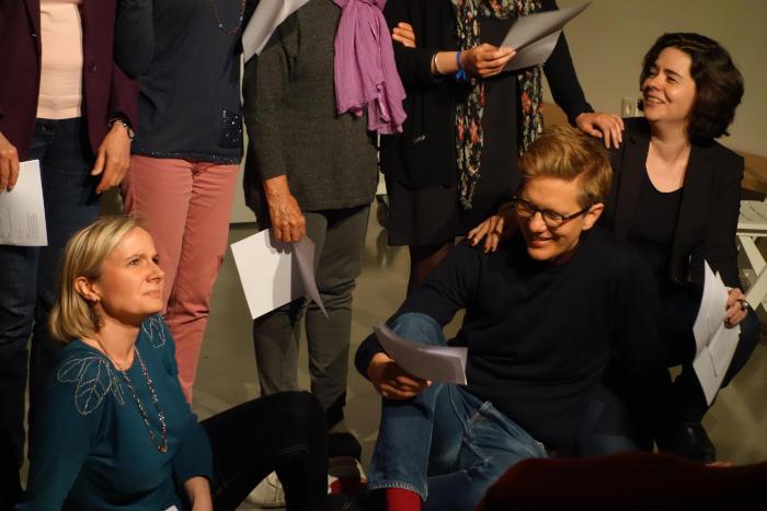 acteurs assis sur la scène répétant leur texte