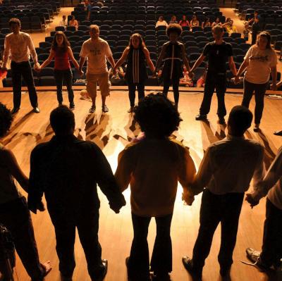 groupes de jeunes sur une scène se tenant la main