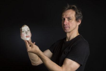 homme tenant un visage de femme sculpté et cassé