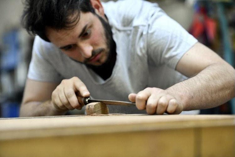 homme travaillant une pièce de bois avec une lime de menuisier