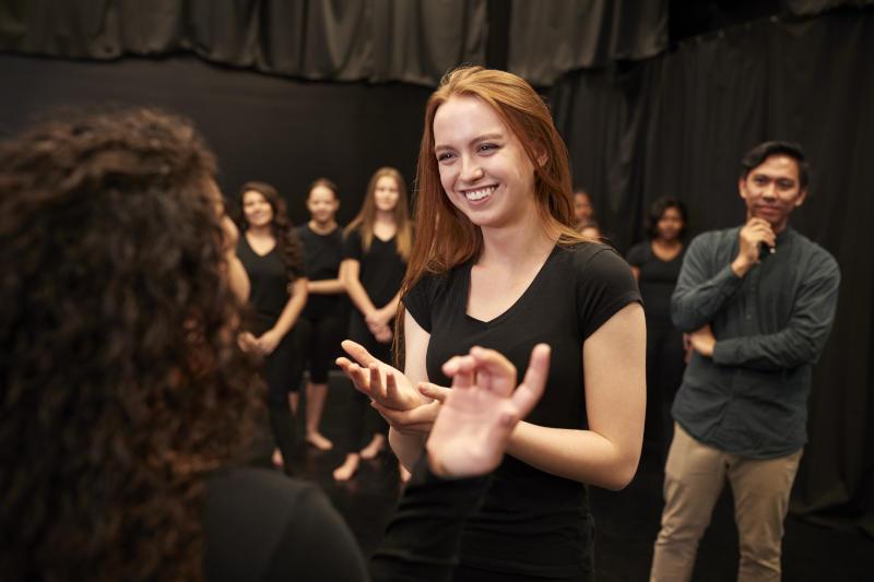 femmes en train de discuter pendant un atelier théâtre avec un prof derrière qui regarde