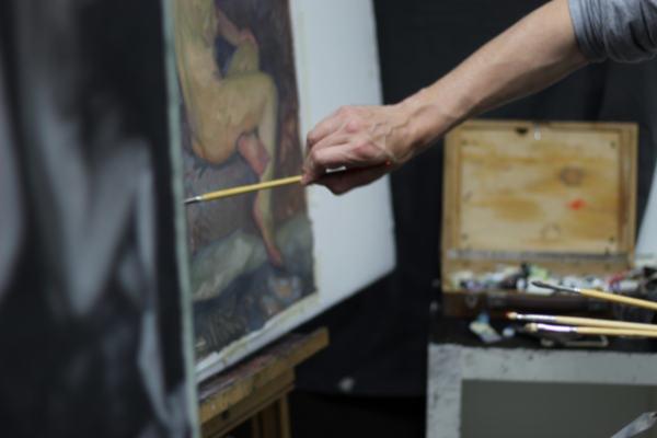 main et bras d'un peintre en train d'appuyer son pinceau contre la toile
