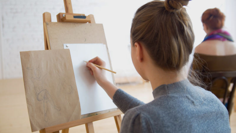 Two female artists sketching model in bright drawing class