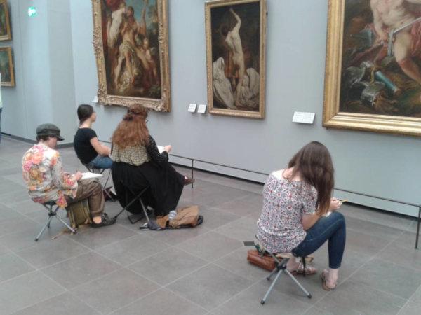dessinateurs assis devant des tableaux du louvre