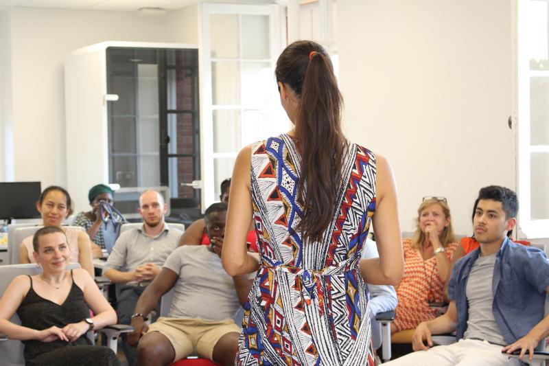 femme de dos parlant à un auditoire