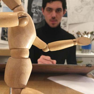 dessinateur face à bonhomme en bois